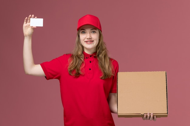 Female courier in red uniform holding white card and food box on pink, uniform service delivery worker job