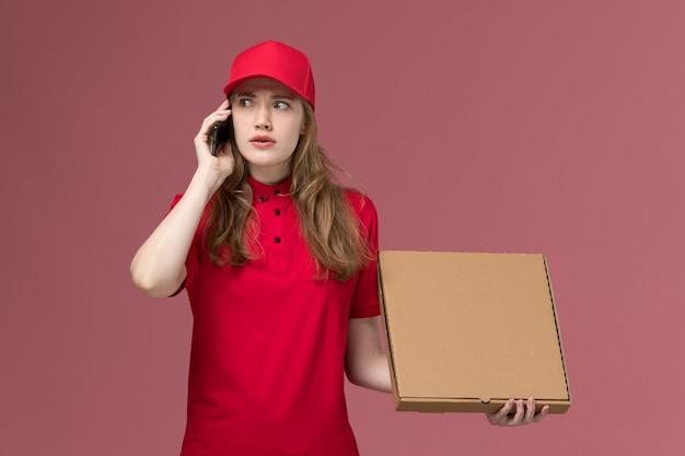 Corriere femminile in uniforme rossa parlando al telefono tenendo la scatola di cibo in rosa, lavoro di lavoratore di consegna del servizio uniforme