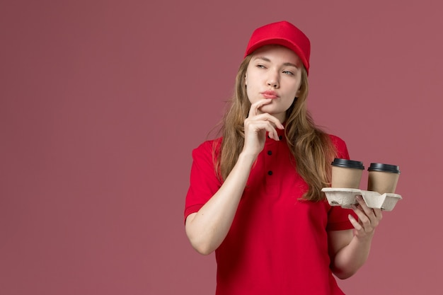 Female courier in red uniform with thinking expression holding coffee cups on pink, uniform service delivery job worker