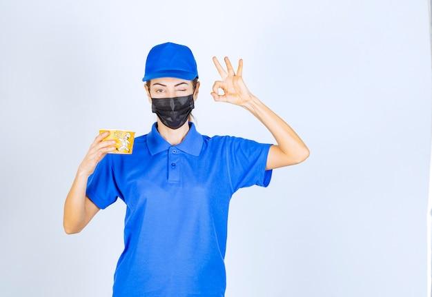 Corriere femminile del ristorante in uniforme blu e maschera facciale che consegna un cibo da asporto e garantisce il buon gusto.