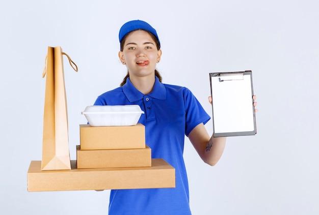 Женщина-курьер высовывает свою длинную куртку и показывает папку, держа пластиковую миску, коробки и сумку перед белой стеной.