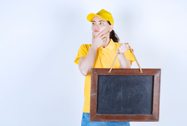 Женщина-курьер думает, прикладывая руку к подбородку, держа доску для письма в левой руке перед белой стеной