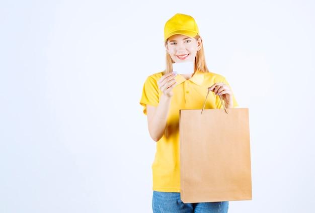 女性の宅配便は、白い壁の前で彼女の買い物袋を笑顔で保持しながら彼女のカードを示しています