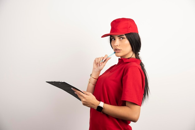 ペンとクリップボードで白い背景の上に立っている女性の宅配便。高品質の写真