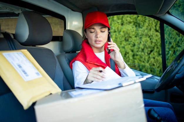 Женский курьер разговаривает по телефону и проверяет посылки перед доставкой.