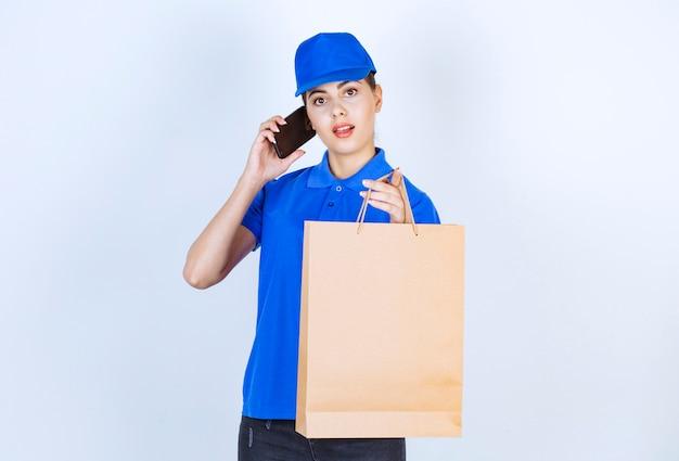 ペーパークラフトバッグを運ぶ携帯電話を介して話している女性の宅配便。