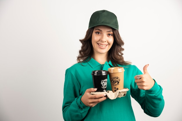 Female courier in uniform holding takeaway coffee and giving thumbs up.