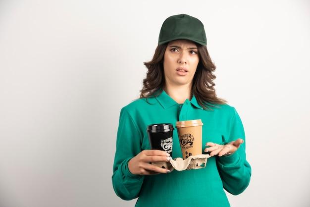 Corriere femminile in uniforme che tiene caffè da asporto con espressione pazza.