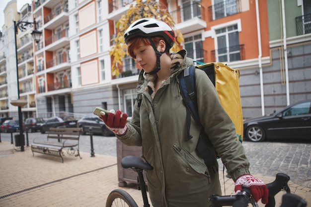 Female courier wearing delivery bag, using smart phone while cycling in the city for work