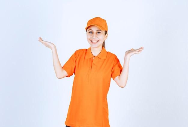オレンジ色のユニフォームと両側を指すキャップを身に着けている女性の宅配便。