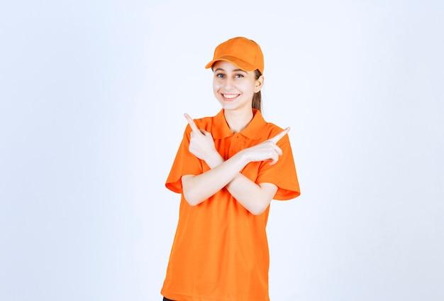 주황색 유니폼과 모자 양쪽을 가리키는 여성 택배.