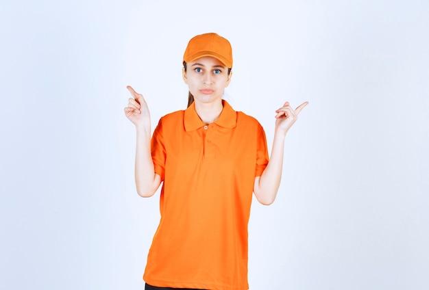 주황색 유니폼을 입고 양쪽을 가리키는 모자를 쓴 여성 택배.