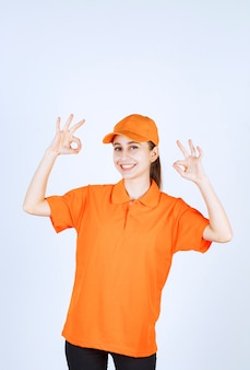 オレンジ色のユニフォームとキャップを身に着けている女性の宅配便は大丈夫な手のサインを示しています