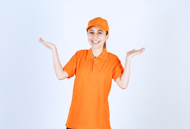 Female courier wearing orange uniform and cap pointing at both sides.