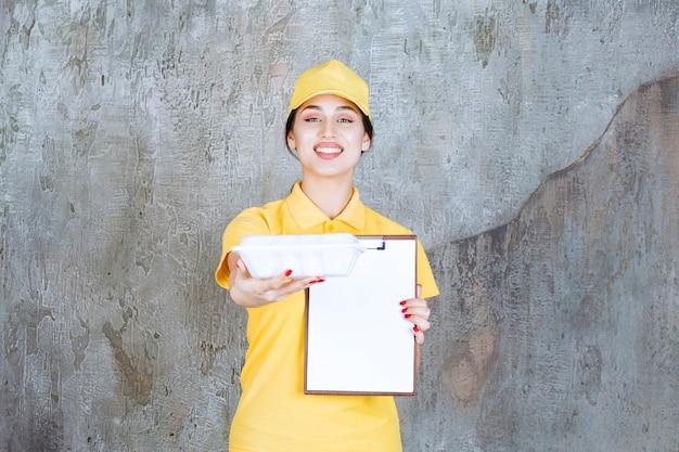 Курьер-женщина в желтой форме доставляет коробку с едой на вынос и просит подписать