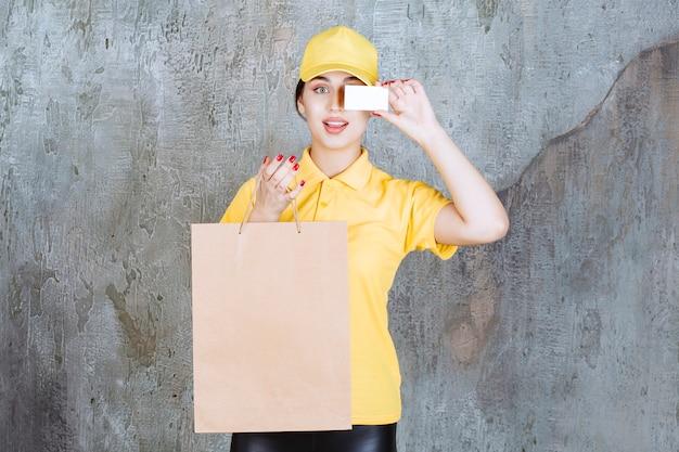 Corriere femminile che indossa un'uniforme gialla che consegna una borsa della spesa di cartone e presenta il suo biglietto da visita.