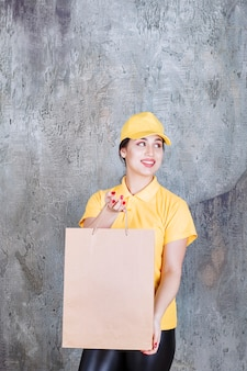 Female courier wearing yellow uniform delivering a cardboard shopping bag.