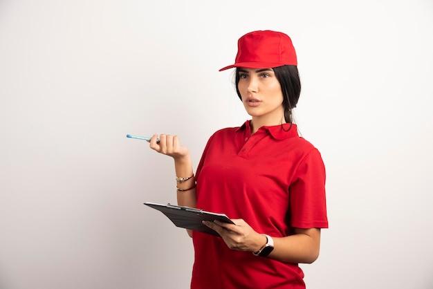 Женский курьер с буфером обмена, думая о чем-то. фото высокого качества