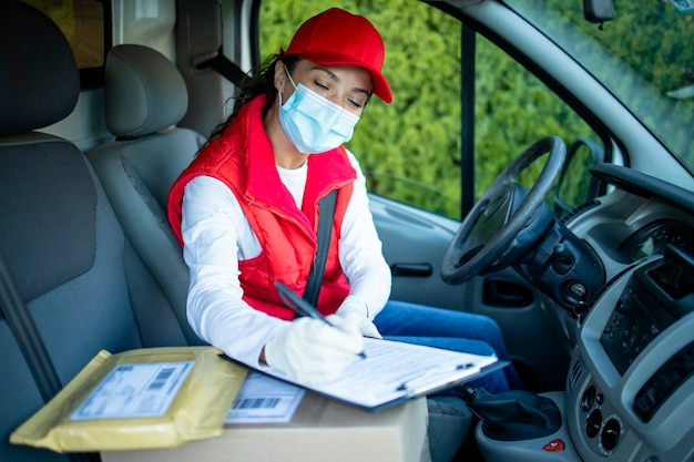 Курьер-женщина с защитой за рулем фургона и доставляет посылки во время пандемии covid19
