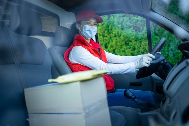 Женский курьер с защитной маской, доставляющий посылки во время пандемии коронавируса или covid19