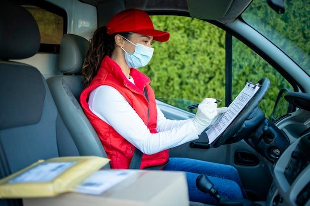 Женский курьер с защитной маской доставляет груз во время пандемии коронавируса