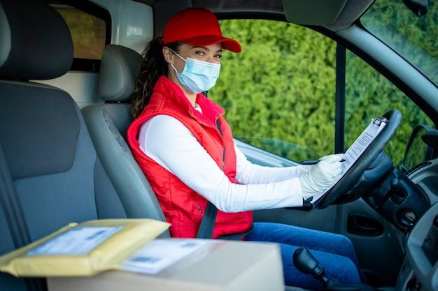 Курьер-женщина в защитной маске водит фургон и доставляет посылки во время пандемии covid19