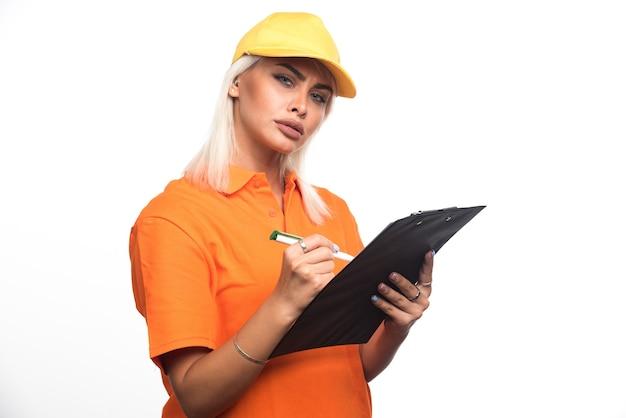 흰색 바탕에 노트북에 순서를 작성하는 여성 택배. 고품질 사진