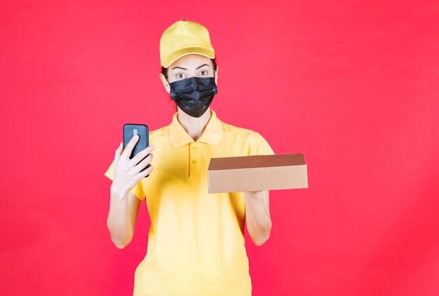 Corriere femminile in uniforme gialla e maschera nera che tiene la scatola di cartone e fa una videochiamata o prende ordini tramite smartphone, mentre sembra confuso