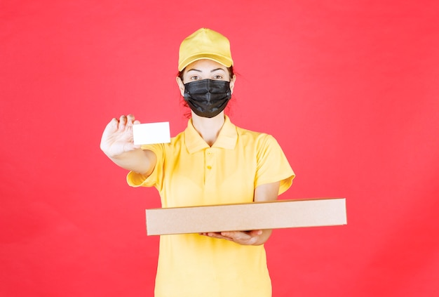 Female courier in yellow uniform and black mask holding a cardboard box and presenting her business card
