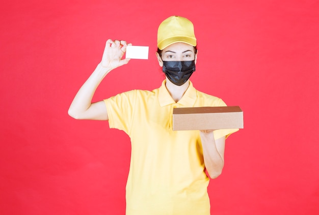 Female courier in yellow uniform and black mask holding the cardboard box and presenting her business card