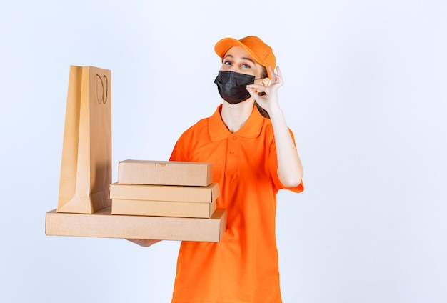 Female courier in yellow uniform and black mask holding multiple cardboard parcels and shopping bag and showing positive hand sign.