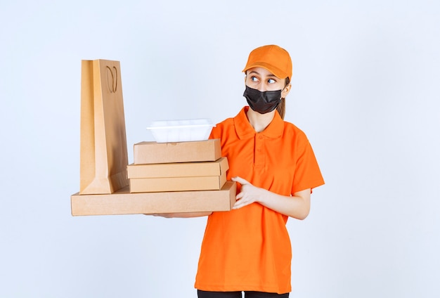 Female courier in yellow uniform and black mask holding multiple cardboard parcels, takeaway box and shopping bag while looking confused and thoughtful.