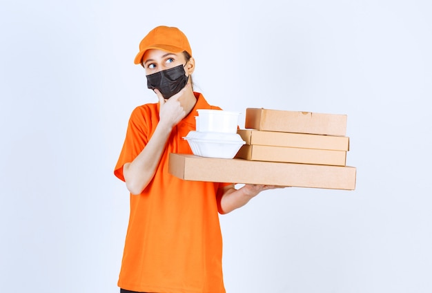 Female courier in yellow uniform and black mask holding multiple cardboard parcels and takeaway boxes and looks confused and thoughtful.