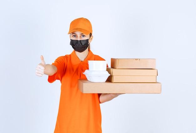 Corriere femminile in uniforme gialla e maschera nera che tiene più pacchi di cartone e scatole da asporto mentre indica qualcosa.