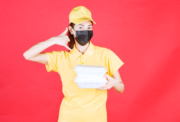 Female courier in yellow uniform and black mask holding multiple takeaway packages and asking for a call