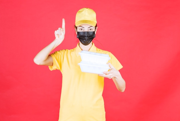 Corriere femminile in uniforme gialla e maschera nera che tiene più pacchi da asporto e ha una buona idea