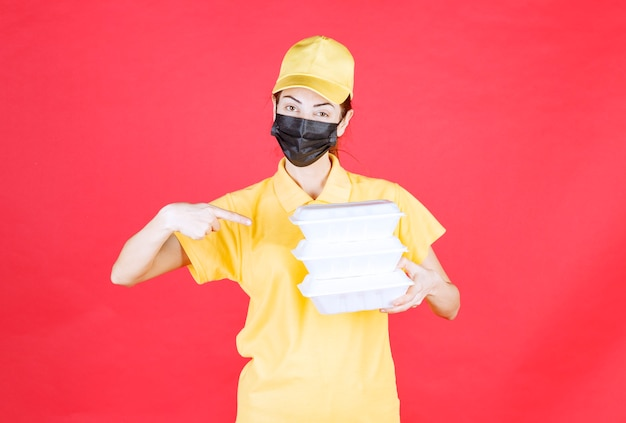 Female courier in yellow uniform and black mask holding multiple takeaway packages and presenting the signature list
