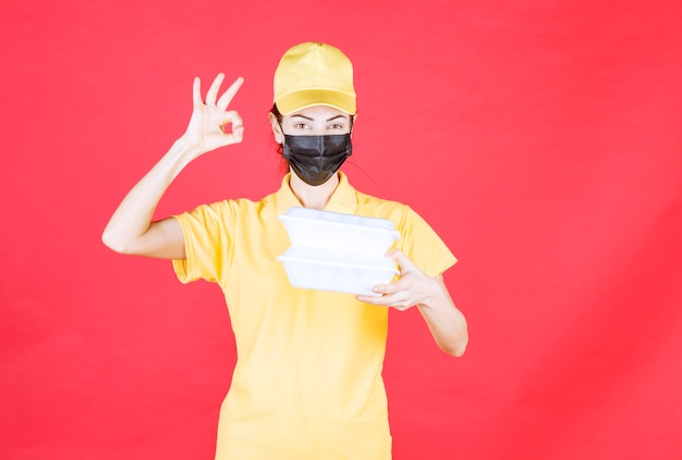 Female courier in yellow uniform and black mask holding multiple takeaway packages and showing positive hand sign