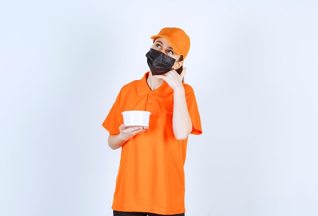 Corriere femminile in uniforme gialla e maschera nera che tiene un bicchiere di plastica e chiede una chiamata