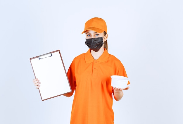 Female courier in yellow uniform and black mask holding a plastic cup and customer list .