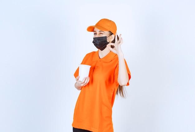 Corriere femminile in uniforme gialla e maschera nera che tiene una tazza di plastica da asporto e si gode il gusto.