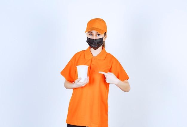 Corriere femminile in uniforme gialla e maschera nera che tiene una tazza di plastica da asporto e la indica.
