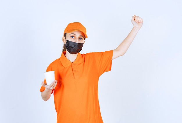 Female courier in yellow uniform and black mask holding a takeaway drink and showing her fist.