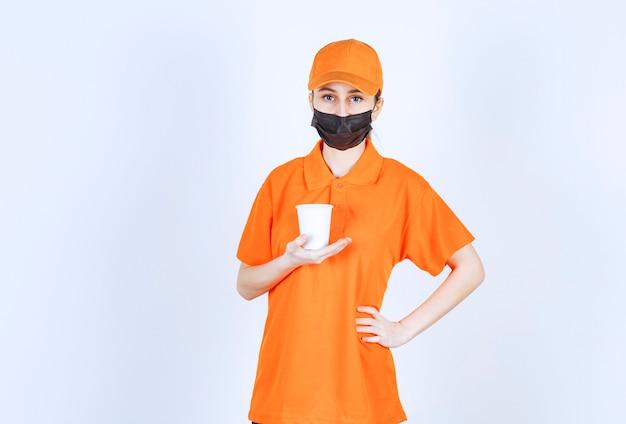 Corriere femminile in uniforme gialla e maschera nera che tiene una bevanda da asporto.