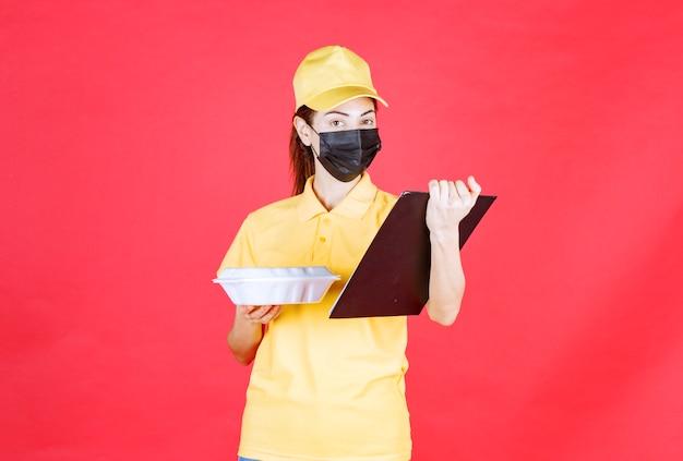 Corriere femminile in uniforme gialla e maschera nera che tiene un pacco da asporto e legge l'elenco dei clienti