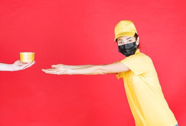 Il corriere femminile in uniforme gialla e maschera nera sta ricevendo una tazza di noodles per la consegna e desidera ardentemente che le sue braccia lo prendano