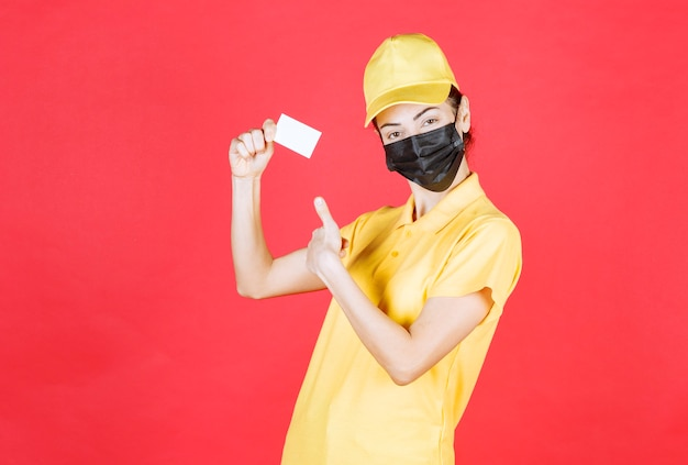 Female courier in yellow uniform and black mask presenting her business card and showing thumb up