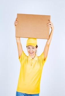 Il corriere femminile in uniforme gialla ha consegnato un pacco di cartone all'indirizzo giusto.