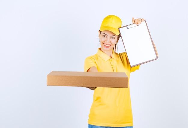 Il corriere femminile in uniforme gialla ha consegnato un pacco e ha chiesto al cliente di firmare.
