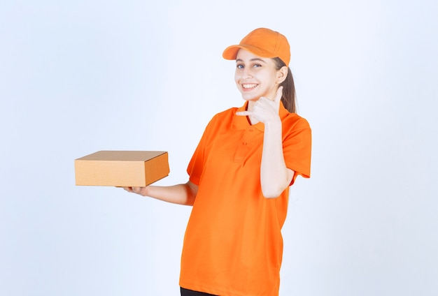 Female courier in yellow uniform delivering a cardboard box .